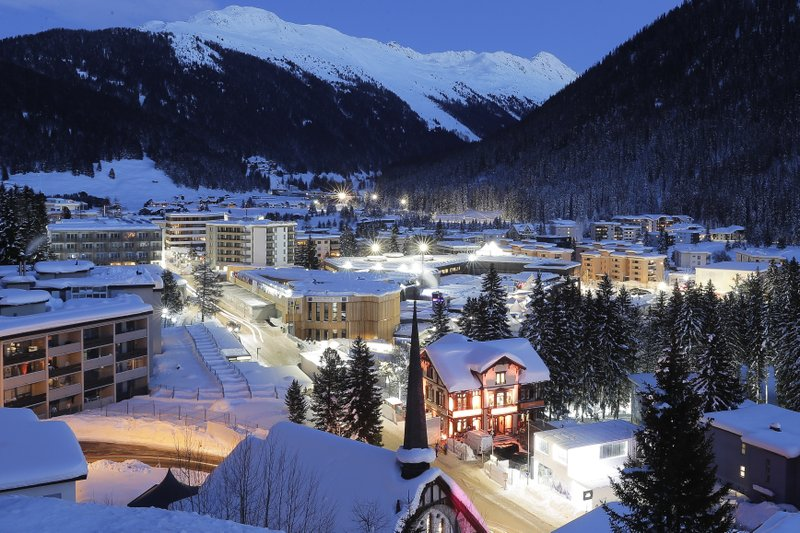 A view of the congress center, the building in center, which hosts the World Economic Forum, WEF, illuminated by street lights at the eve of the annual meeting of the forum, in Davos, Sunday, Jan. (AP Photo/Markus Schreiber)