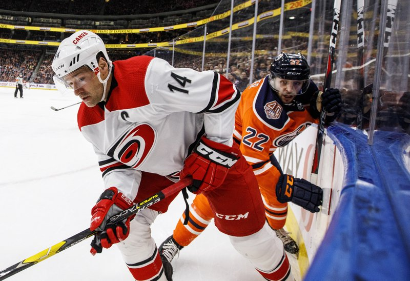 Carolina Hurricanes' Justin Williams (14) and Edmonton Oilers' Tobias Rieder (22) battle for the puck during the first period of an NHL hockey game, Sunday, Jan. (Jason Franson/The Canadian Press via AP)
