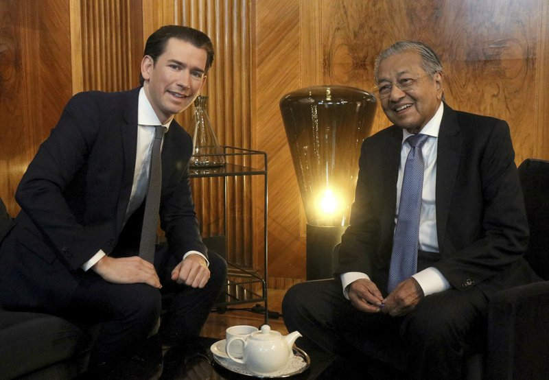 Austrian Chancellor Sebastian Kurz talks with Malaysia's Prime Minister Mahathir Mohamad, from left, at the federal chancellery in Vienna, Austria, Monday, Jan. (AP Photo/Ronald Zak)