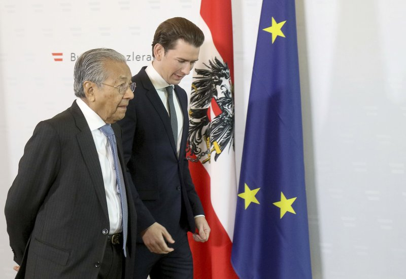 Austrian Chancellor Sebastian Kurz, right, welcomes Malaysia's Prime Minister Mahathir Mohamad, left, for a meeting at the federal chancellery in Vienna, Austria, Monday, Jan. (AP Photo/Ronald Zak)