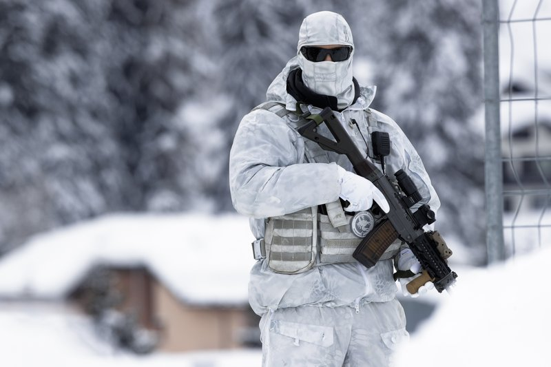 An armed Swiss police officer stands guard on the roof of the congress center where the annual meeting of the World Economic Forum, WEF, take place in in Davos, Monday, Jan. (AP Photo/Markus Schreiber)