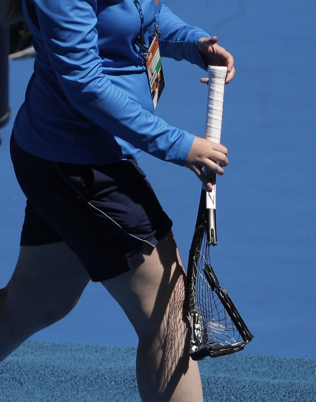 A court attendant takes the smashed racket of Germany's Alexander Zverev away during his fourth round match against Canada's Milos Raonic at the Australian Open tennis championships in Melbourne, Australia, Monday, Jan. (AP Photo/Mark Schiefelbein)