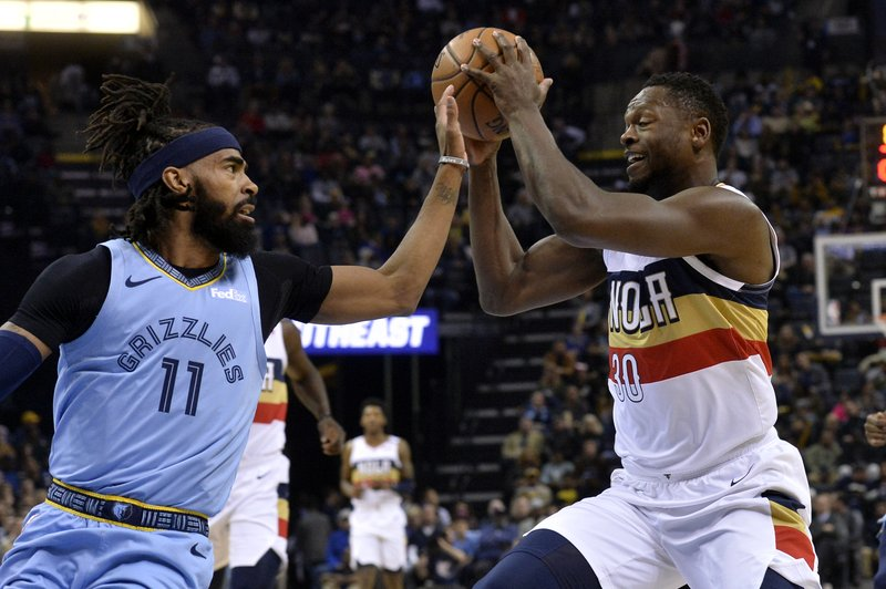 New Orleans Pelicans forward Julius Randle (30) controls the ball against Memphis Grizzlies guard Mike Conley (11) in the first half of an NBA basketball game Monday, Jan. (AP Photo/Brandon Dill)