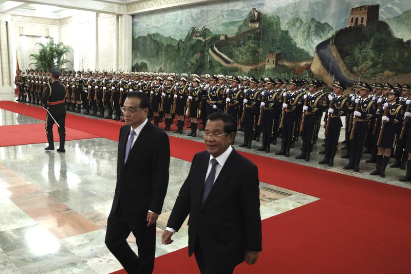Cambodian Prime Minister Hun Sen, right, walks with Chinese Premier Li Keqiang during a welcome ceremony at the Great Hall of the People in Beijing, China, Tuesday, Jan. (AP Photo/Ng Han Guan)
