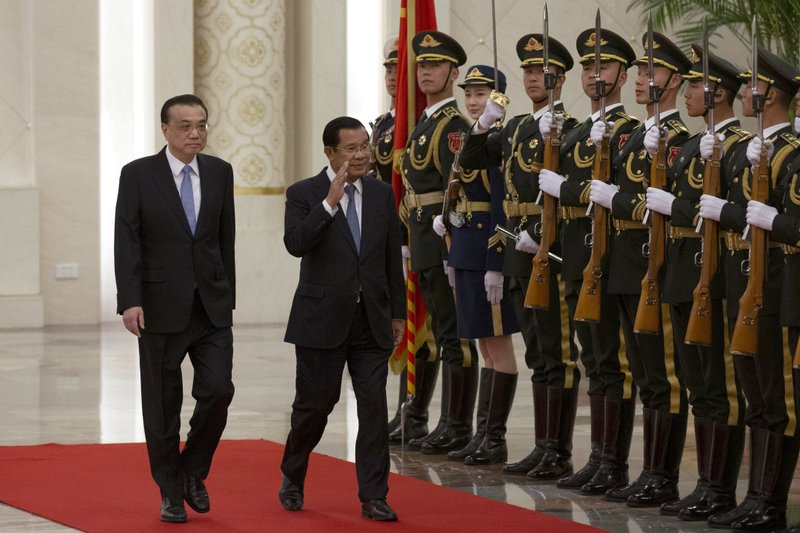 Cambodian Prime Minister Hun Sen, second left, reacts as he inspects a Chinese guard of honor with Chinese Premier Li Keqiang at the Great Hall of the People in Beijing, China, Tuesday, Jan. (AP Photo/Ng Han Guan)