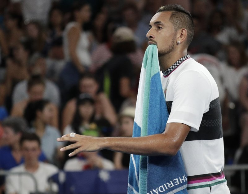 Australia's Nick Kyrgios walks with his towel in his mouth as he changes ends during his first round match against Canada's Milos Raonic at the Australian Open tennis championships in Melbourne, Australia, Tuesday, Jan. (AP Photo/Aaron Favila)