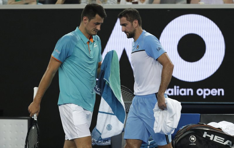 Croatia's Marin Cilic, right, and Australia's Bernard Tomic change ends during their first round match at the Australian Open tennis championships in Melbourne, Australia, Monday, Jan. (AP Photo/Kin Cheung)