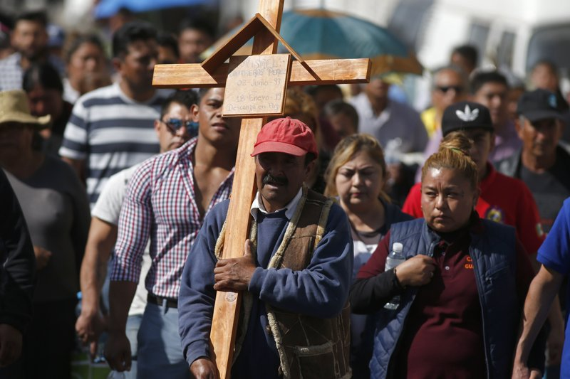 A man carries a cross during the funeral procession of a person who died when a gas pipeline exploded in the village of Tlahuelilpan, Mexico, Sunday Jan. (AP Photo/Claudio Cruz)