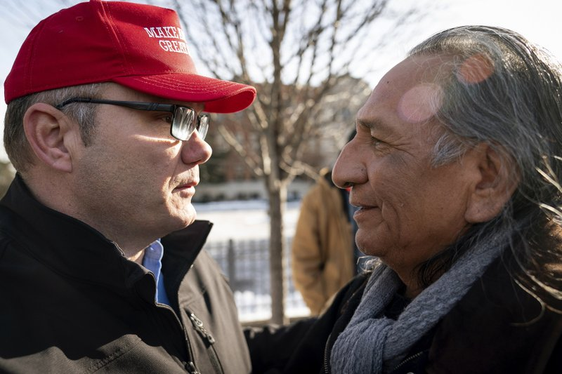 Guy Jones, left, and a supporter of President Donald Trump named Don embrace during a gathering of Native American supporters in front of the Catholic Diocese of Covington in Covington, Ky. (AP Photo/Bryan Woolston)