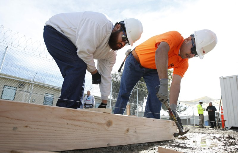 Youthful offenders Siegmond Navar, left and Gabriel Andalon construct a frame to hold concrete at one of the vocational classes at the O. (AP Photo/Rich Pedroncelli)