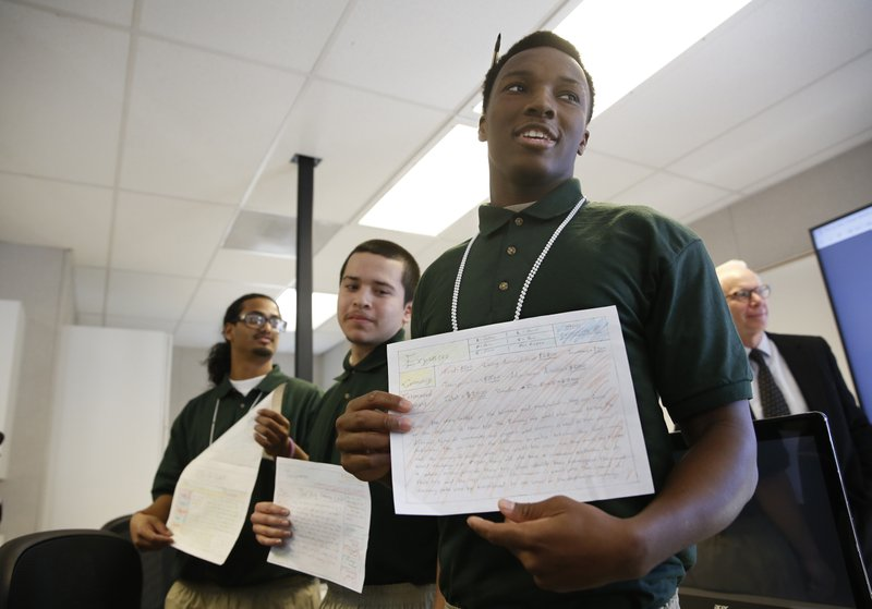 Derrick McDougal, right, a youthful offender at the O.H. Close Youth Correctional Facility, displays a website he helped design, at a computer coding class, Tuesday, Jan. (AP Photo/Rich Pedroncelli)