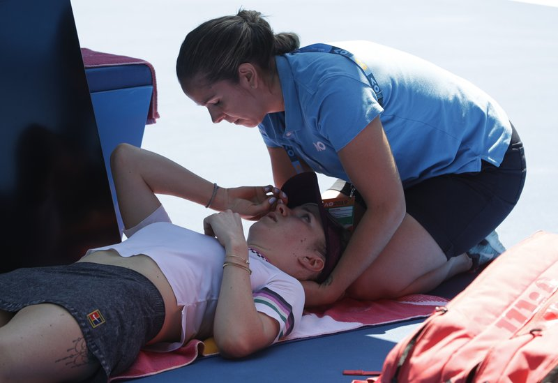 Ukraine's Elina Svitolina receives treatment from a trainer during her quarterfinal against Japan's Naomi Osaka at the Australian Open tennis championships in Melbourne, Australia, Wednesday, Jan. (AP Photo/Mark Schiefelbein)