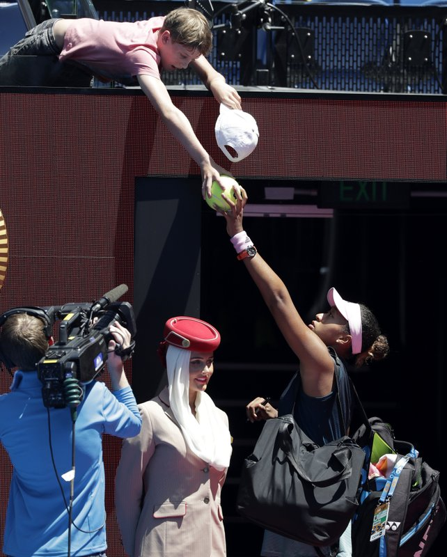 Japan's Naomi Osaka signs autographs for a fan as she leaves Rod Laver Arena following her quarterfinal win over Ukraine's Elina Svitolina at the Australian Open tennis championships in Melbourne, Australia, Wednesday, Jan. (AP Photo/Kin Cheung)