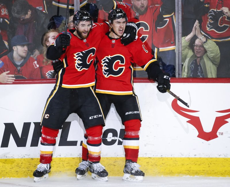 Calgary Flames' Mikael Backlund, right, of Sweden, celebrates his game-winning goal with teammate T.J. (Jeff McIntosh/The Canadian Press via AP)