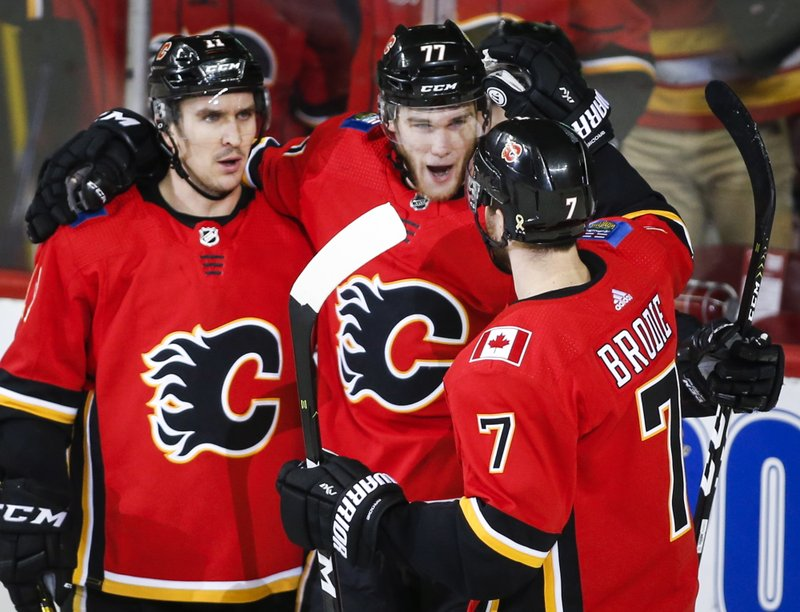 Calgary Flames' Mark Jankowski, centre, celebrates his goal with teammates during second period NHL hockey action against the Carolina Hurricanes, in Calgary, Tuesday, Jan. (Jeff McIntosh/The Canadian Press via AP)