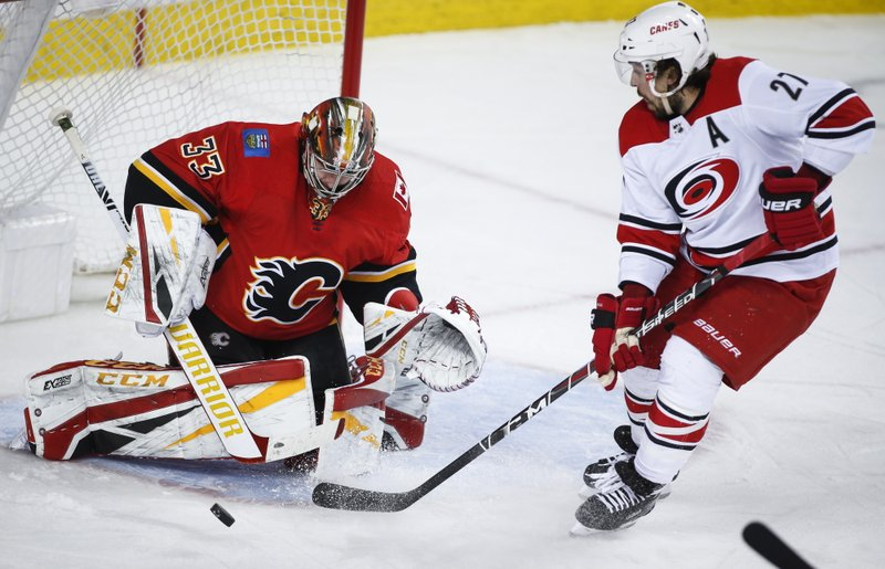 Carolina Hurricanes' Justin Faulk, right, has his shot deflected by Calgary Flames goalie David Rittich, of the Czech Republic, during second period NHL hockey action in Calgary, Tuesday, Jan. (Jeff McIntosh/The Canadian Press via AP)