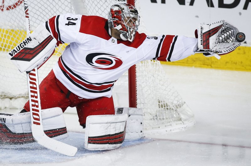 Carolina Hurricanes goalie Petr Mrazek, of the Czech Republic, grabs for the puck during second period NHL hockey action against the Calgary Flames, in Calgary, Tuesday, Jan. (Jeff McIntosh/The Canadian Press via AP)