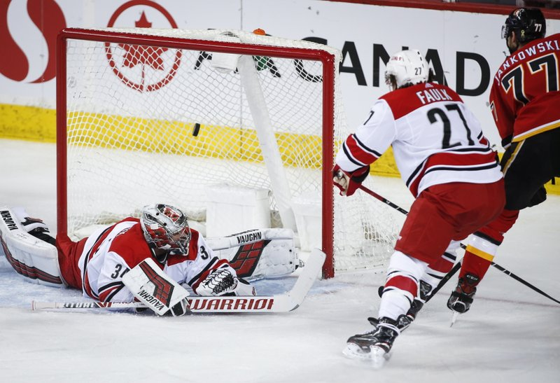 Carolina Hurricanes goalie Petr Mrazek, left, of the Czech Republic, lets in a goal from Calgary Flames' Mark Jankowski, right, during second period NHL hockey action in Calgary, Tuesday, Jan. (Jeff McIntosh/The Canadian Press via AP)