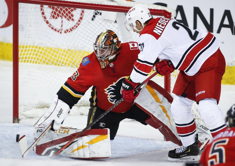Carolina Hurricanes' Nino Niederreiter, right, of Switzerland, has his shot go wide past Calgary Flames goalie David Rittich, of the Czech Republic, during first period NHL hockey action in Calgary, Tuesday, Jan. (Jeff McIntosh/The Canadian Press via AP)