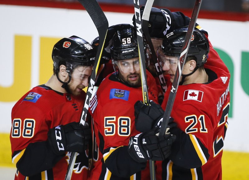 Calgary Flames' Oliver Kylington, centre, of Sweden, celebrates his goal with teammates Andrew Mangiapane, left, and Garnet Hathaway during first period NHL hockey action against the Carolina Hurricanes, in Calgary, Tuesday, Jan. (Jeff McIntosh/The Canadian Press via AP)
