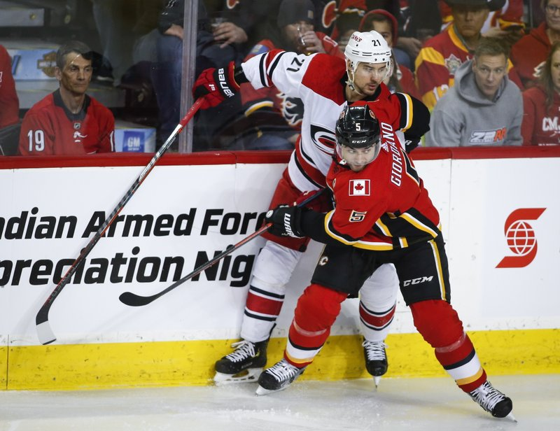 Carolina Hurricanes' Nino Niederreiter, left, of Switzerland, is checked by Calgary Flames' Mark Giordano during first period NHL hockey action in Calgary, Tuesday, Jan. (Jeff McIntosh/The Canadian Press via AP)