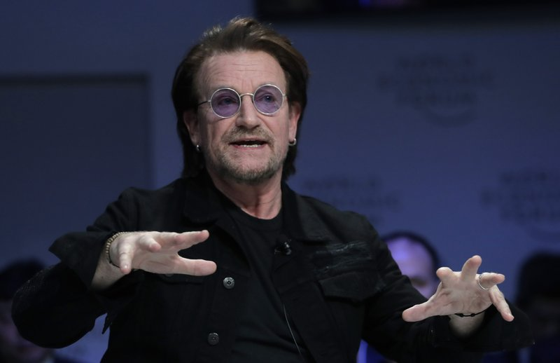 Singer and co-founder of RED Bono gestures while participating in the