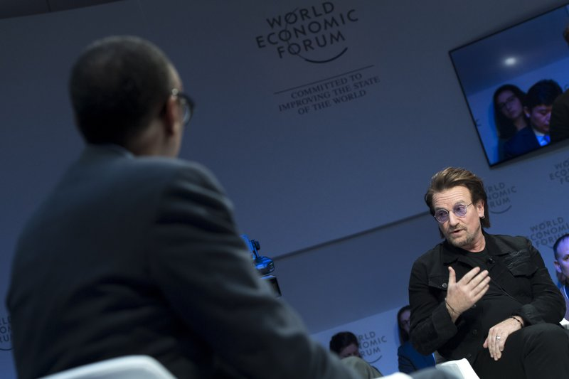 Irish singer Bono, right, speaks in front of Rwanda President Paul Kagame, left, during a panel session during the the 49th Annual Meeting of the World Economic Forum, WEF, in Davos, Switzerland, Wednesday, Jan. (Laurent Gillieron/Keystone via AP)