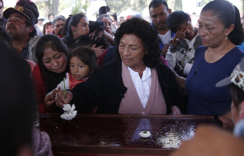 A woman sprinkles holy water, using a flower, on the coffin of a person who died when a gas pipeline exploded in the village of Tlahuelilpan, Mexico, Sunday Jan. (AP Photo/Claudio Cruz)