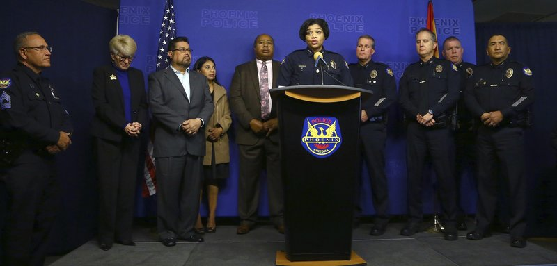 Joined by other police officials and city leaders, Phoenix Police Chief Jeri Williams, center, announces the arrest of Nathan Sutherland, a licensed practical nurse, on one count of sexual assault and one count of vulnerable adult abuse on an incapacitated woman who gave birth last month at a long-term health care facility Wednesday, Jan. (AP Photo/Ross D. Franklin)