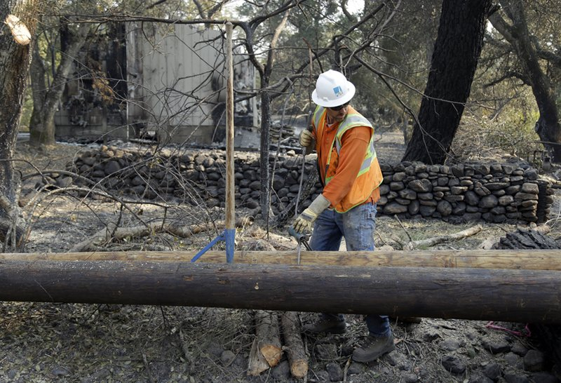 FILE - In this Oct. 18, 2017 file photo, a Pacific Gas & Electric worker replaces power poles destroyed by wildfires in Glen Ellen, Calif. (AP Photo/Ben Margot, file)