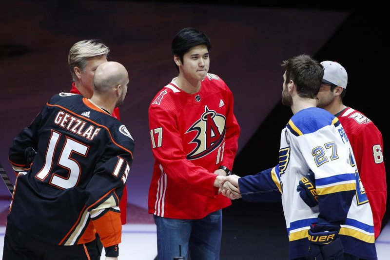Los Angeles Angels pitcher Shohei Ohtani, center, of Japan, shakes hands with St. Louis Blues' Alex Pietrangelo, left, and Anaheim Ducks' Ryan Getzlaf after the ceremonial puck drop before an NHL hockey game, Wednesday, Jan. (AP Photo/Jae C. Hong)