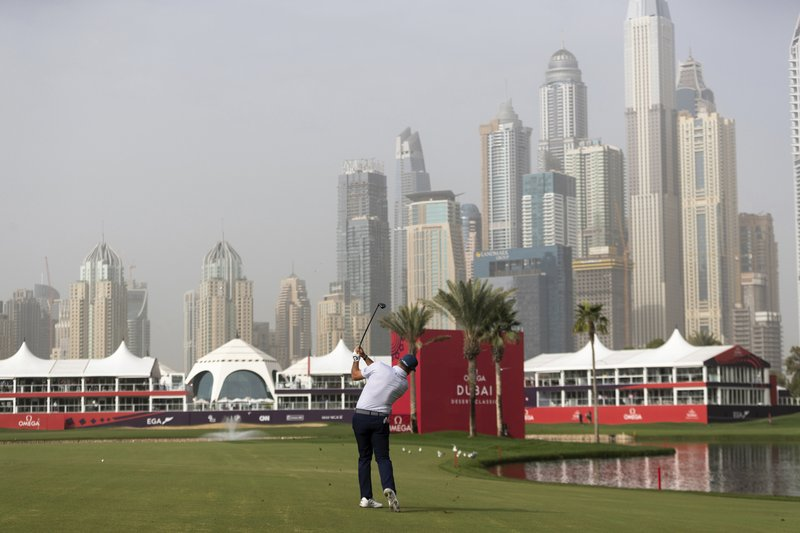 Lee Westwood of Britain hits an approach shot onto the green at the 18th hole during the round one of the Dubai Desert Classic golf tournament in Dubai, United Arab Emirates, Thursday, Jan. (AP Photo/Neville Hopwood)