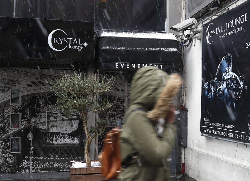 A woman walks past the Crystal Club in Paris, Tuesday Jan.22, 2019. U.S. singer Chris Brown and two other people are in custody in Paris after a woman filed a rape complaint, French officials said Tuesday. (AP Photo/Thibault Camus)