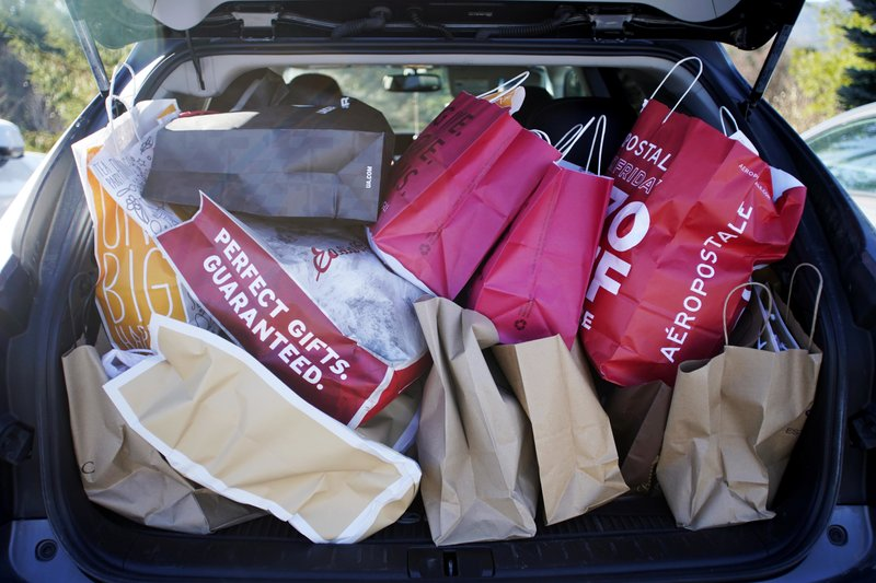 FILE- In this Nov. 23, 2018, file photo shopping bags are stuffed into a car at Prime outlets on Black Friday in Lee, Mass. (Ben Garver/The Berkshire Eagle via AP, File)