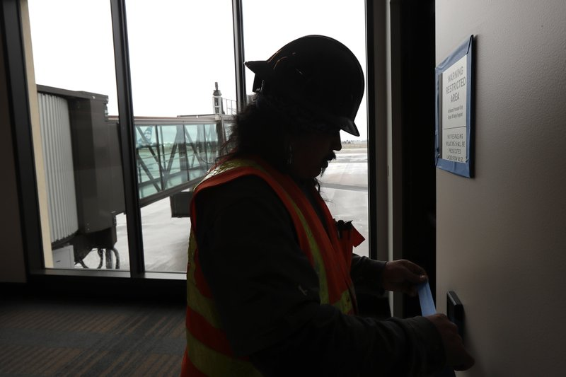 FILE- In this Jan. 23, 2019, file photo Dave McLeod tapes off trim as he prepares to paint a wall near a gate in the new passenger terminal at Paine Field in Everett, Wash. (AP Photo/Ted S. Warren, File)