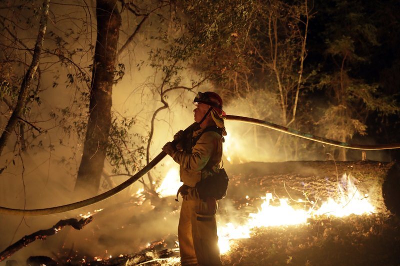 FILE - In this Oct. 14, 2017 file photo, a firefighter holds a water hose while fighting a wildfire in Santa Rosa, Calif. (AP Photo/Marcio Jose Sanchez, File)