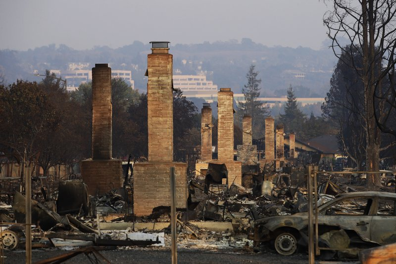FILE - This Oct. 13, 2017 file photo shows a row of chimneys standing in a neighborhood devastated by the Tubbs fire near Santa Rosa, Calif. (AP Photo/Jae C. Hong, File)