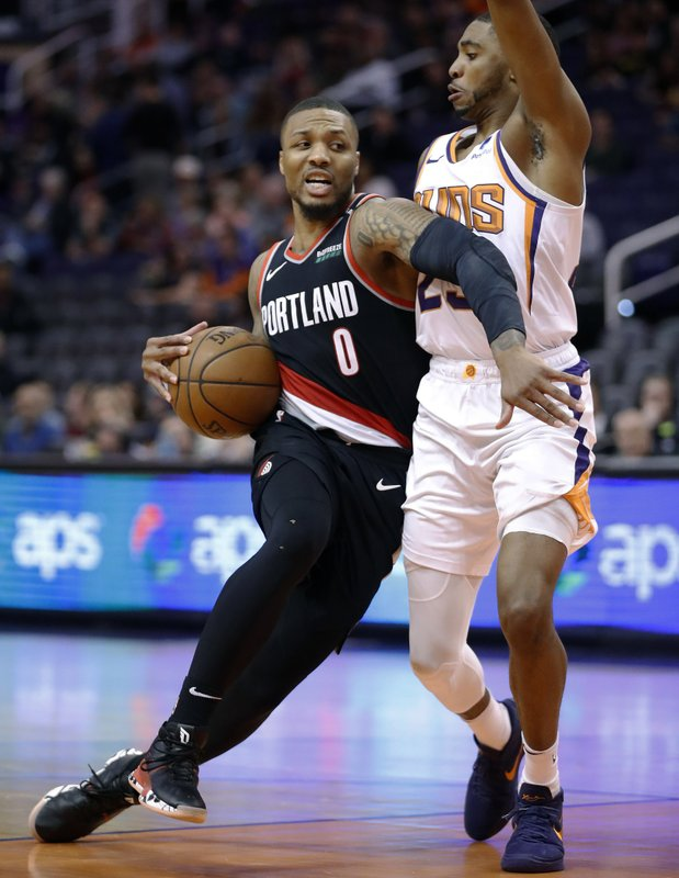 Portland Trail Blazers guard Damian Lillard (0) drives around Phoenix Suns forward Mikal Bridges during the second half of an NBA basketball game Thursday, Jan. (AP Photo/Matt York)