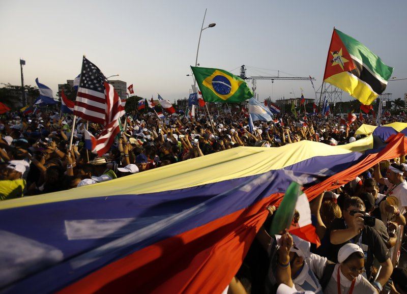 Thousands of pilgrims wave their national flags as Pope Francis arrives for a welcoming ceremony to open his participation in the church's World Youth Day festivities in Panama City, Thursday, Jan. (AP Photo/Rebecca Blackwell)
