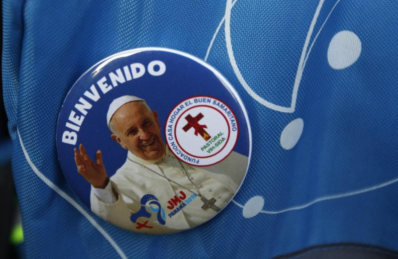 A pilgrim wears a pin of Pope Francis during a welcoming ceremony to open his participation in the church's World Youth Day festivities in Panama City, Thursday, Jan. (AP Photo/Rebecca Blackwell)
