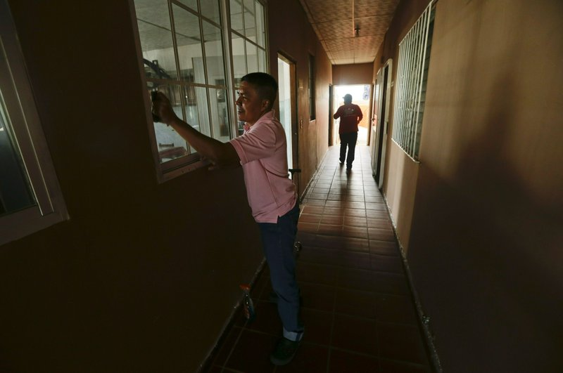 Cesar cleans a window at the Good Samaritan home, a Roman Catholic-run shelter for HIV and AIDS patients where he lives in Panama City, Saturday, Jan. (AP Photo/Arnulfo Franco)