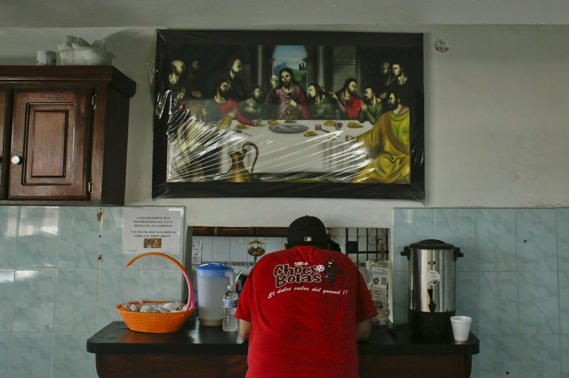 A volunteer stands under an image of the Last Supper, where there's a small window, inside the kitchen of the Good Samaritan home, a Roman Catholic-run shelter for HIV and AIDS patients in Panama City, Saturday, Jan. (AP Photo/Arnulfo Franco)