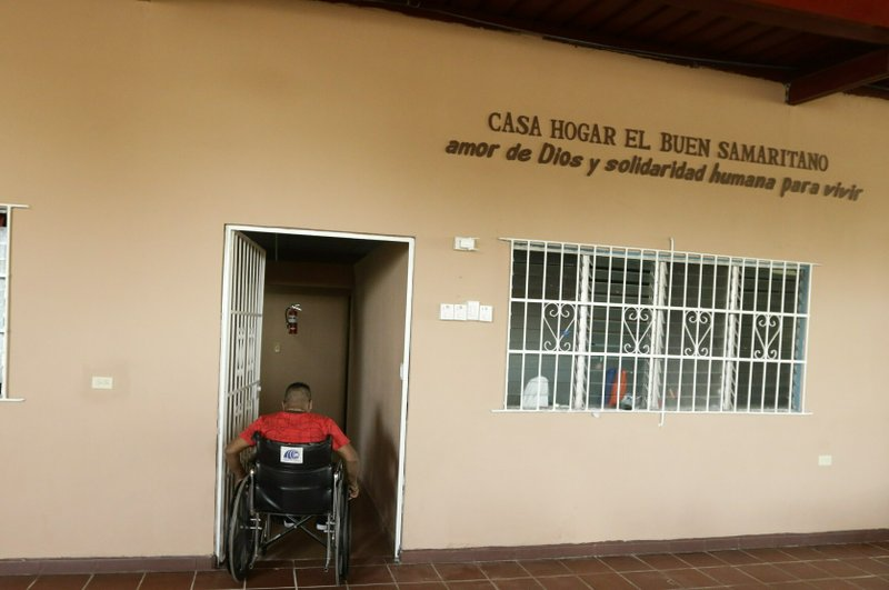 Raul Tubri enters an area of the Good Samaritan home, a Roman Catholic-run shelter for HIV and AIDS patients, as he returns to his room in Panama City, Saturday, Jan. (AP Photo/Arnulfo Franco)