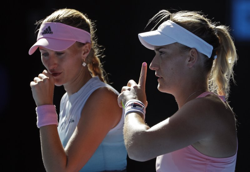 France's Kristina Mladenovic, left, and Hungary's Timea Babos talk during the women's doubles final against China's Zhang Shuai and Australia's Samantha Stosur at the Australian Open tennis championships in Melbourne, Australia, Friday, Jan. (AP Photo/Mark Schiefelbein)