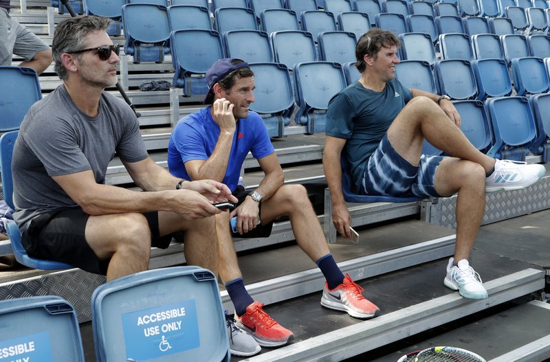 Australian actor Eric Bana, left, former Formula One driver Mark Webber and former US Open tennis champion Pat Rafter, right, watch Japan's Naomi Osaka during a practice session at the Australian Open tennis championships in Melbourne, Australia, Friday, Jan. (AP Photo/Mark Baker)