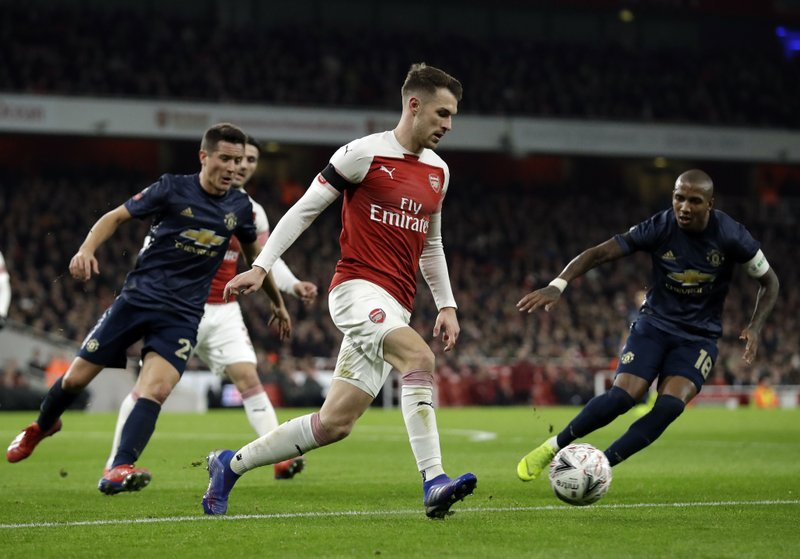 Arsenal's Aaron Ramsey, center, duels for the ball with Manchester United's Ashley Young, right, during the English FA Cup fourth round soccer match between Arsenal and Manchester United at the Emirates stadium in London, Friday, Jan. (AP Photo/Matt Dunham)