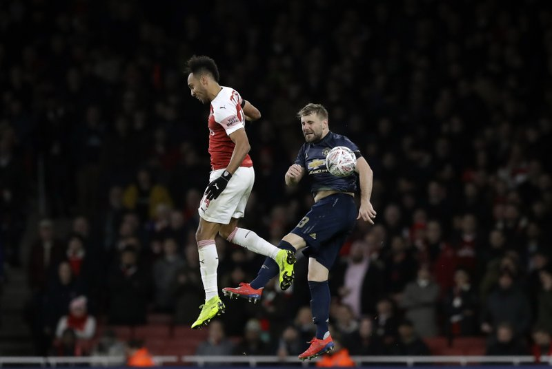 Arsenal's Pierre-Emerick Aubameyang, left, jumps for the ball with Manchester United's Luke Shaw during the English FA Cup fourth round soccer match between Arsenal and Manchester United at the Emirates stadium in London, Friday, Jan. (AP Photo/Matt Dunham)
