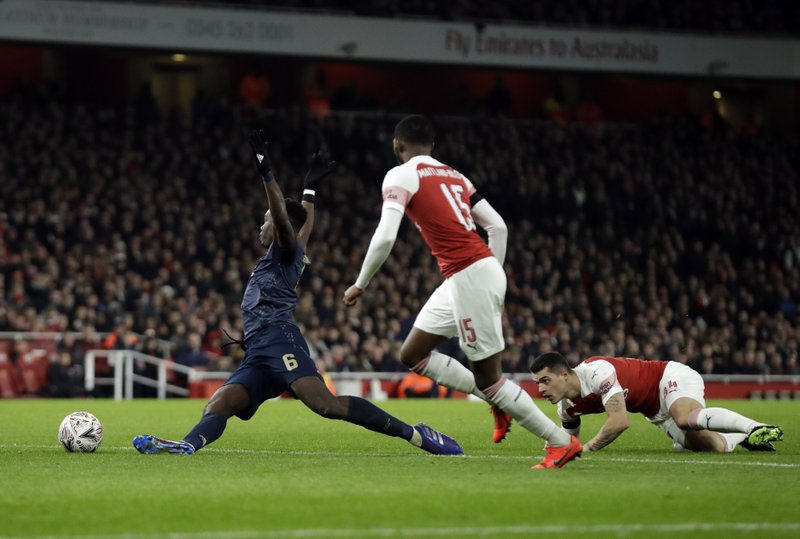 Manchester United's Paul Pogba, left, kicks the ball in front of Arsenal's Ainsley Maitland-Niles, center,, and Arsenal's Granit Xhaka during the English FA Cup fourth round soccer match between Arsenal and Manchester United at the Emirates stadium in London, Friday, Jan. (AP Photo/Matt Dunham)