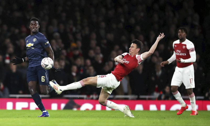 Arsenal's Laurent Koscielny lunges for the ball against Manchester United's Paul Pogba, left, during an English FA Cup fourth round soccer match between Arsenal and Manchester United at the Emirates stadium in London, Friday, Jan. (John Walton/PA via AP)