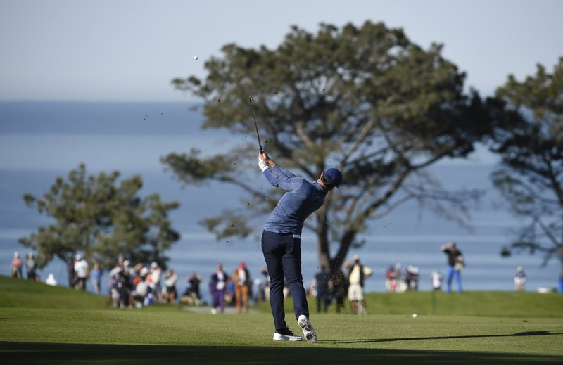 Rory McIlroy, of Northern Ireland, hits his second shot on the 10th hole during the second round of the Farmers Insurance Open golf tournament on the North Course at the Torrey Pines on Friday, Jan. (AP Photo/Denis Poroy)